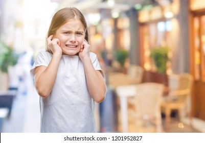 Young beautiful girl over isolated background covering ears with fingers with annoyed expression for the noise of loud music. Deaf concept.