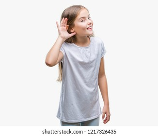 Young beautiful girl over isolated background smiling with hand over ear listening an hearing to rumor or gossip. Deafness concept.