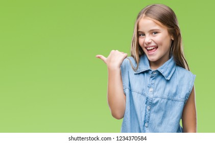 Young beautiful girl over isolated background smiling with happy face looking and pointing to the side with thumb up.