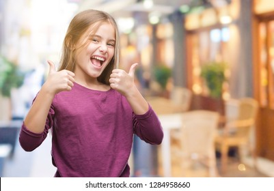 Young beautiful girl over isolated background success sign doing positive gesture with hand, thumbs up smiling and happy. Looking at the camera with cheerful expression, winner gesture.