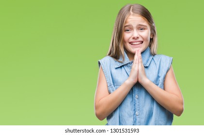 Young beautiful girl over isolated background begging and praying with hands together with hope expression on face very emotional and worried. Asking for forgiveness. Religion concept.