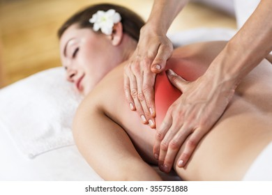 Young beautiful girl with pain lying on massage table and enjoying massage.