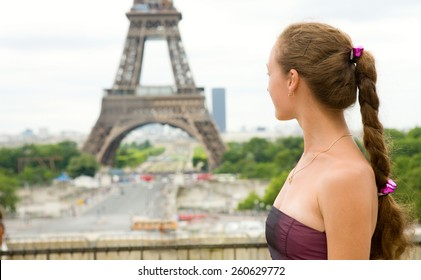 Young beautiful girl in Paris, looking at the Eiffel Tower
