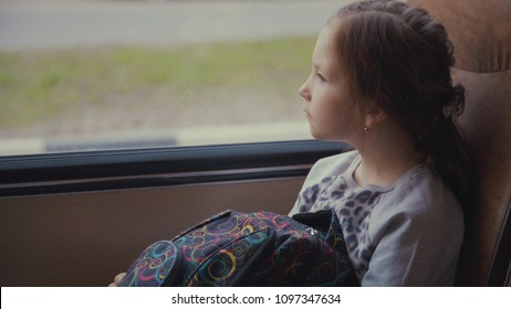 Young, beautiful girl passenger with school bag in the moving school bus looking out the window.