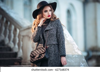 Young beautiful girl with perfect make-up, red lips, wearing a black hat and grey coat, black dress, posing in city.