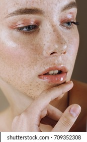 Young beautiful girl with perfect skin and freckles touched her lips