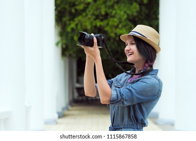 Young beautiful girl photographer taking a photograph of a close-up. Against the background of a green wall of plants. Holds a vintage camera. The mirrorless camera.