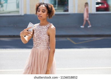 Young beautiful girl is photographing herself on a mobile phone on the street
