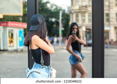 A young beautiful girl photographs with a smartphone her reflection in the mirror. Summer day.
