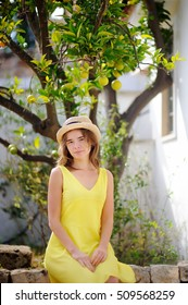 Young beautiful girl picking fresh ripe limes or lemons in sunny tree garden in Italy. Female farmer working in fruit orchard