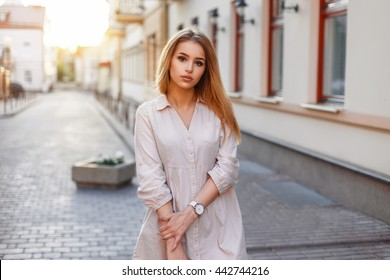 Young beautiful girl in pink dress walking in the city at sunset