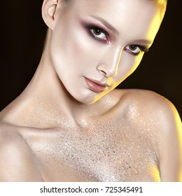 Young beautiful girl with pink make-up and glitter in decolletage zone. Beauty close-up portrait