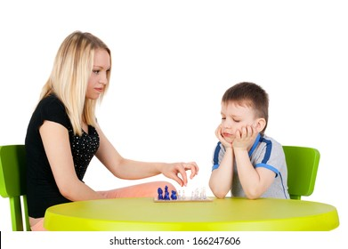 young beautiful girl playing chess with the handsome little boy