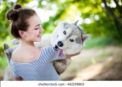 Young beautiful girl playing with a dog. Playing with the dog on the park. Close-up portrait. Siberian husky.