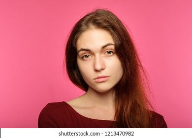 young beautiful girl with a poker face. lack of emotion. portrait of indifferent cold icy nonchalant woman on pink background.