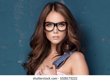 5359531fc04d Young beautiful girl posing in fashionable eyeglasses, standing on blue  background, looking at camera
