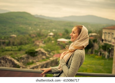 Young, beautiful girl posing in Gelati monastery mountains in the background