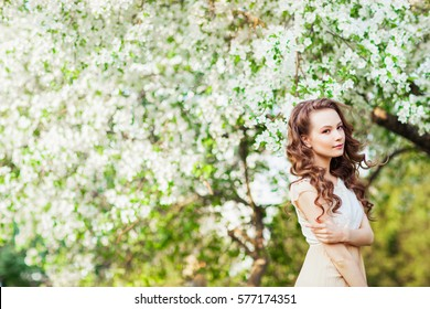 Young beautiful girl posing near apple-tree in blossom