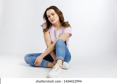 Young beautiful girl posing on white background. Emotions and gestures.