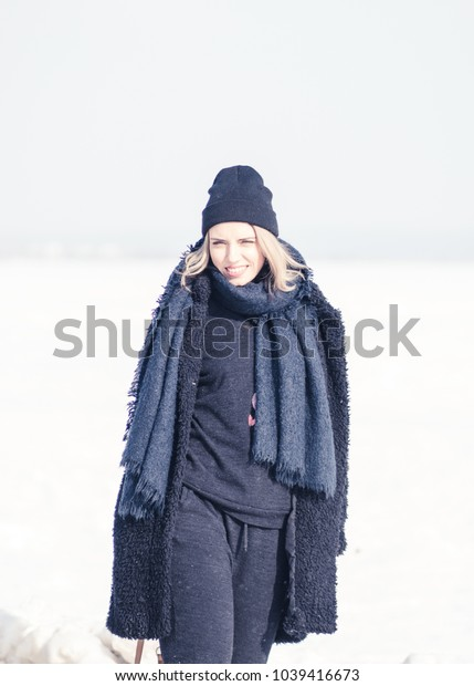 young beautiful girl posing outdoors in winter in a black coat