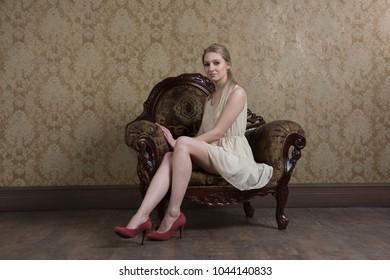 young beautiful girl posing in studio in white dress, sitting in armchair