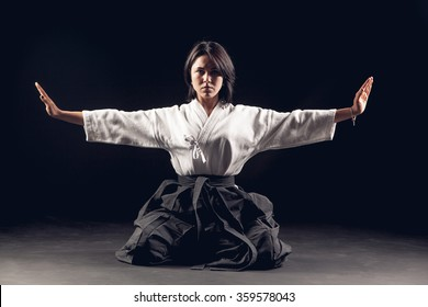 Young, beautiful girl  practicing Aikido in a dark gym