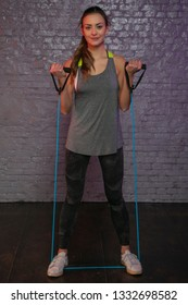 young beautiful girl practicing at the gym with rubbers