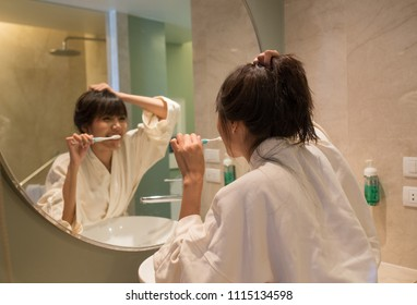 Young beautiful girl preparing to brush her teeth in the bathroom