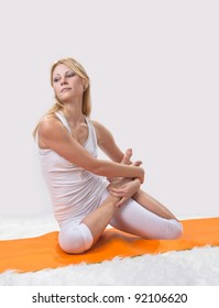 Young beautiful girl is professionally engaged in yoga