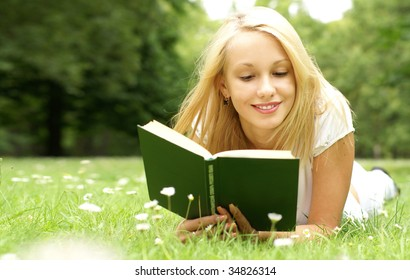 Young beautiful girl reading a book outdoor