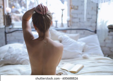 Young beautiful Girl reading book in romantic boho bedroom interior in the morning. Blond sexy naked female Boudoir photo sitting in lotus position with her back to camera in front of large window.