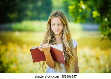 Young beautiful girl reads red book, against green summer garden.