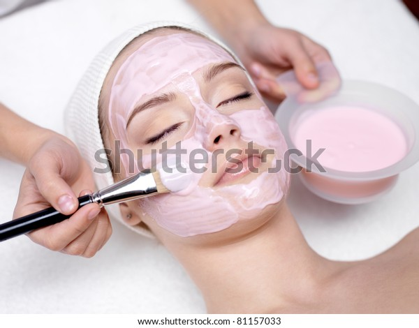 Young beautiful girl receiving pink facial mask in spa beauty salon - indoors