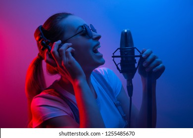 Young beautiful girl records vocals, show business, DJ, party, pop music