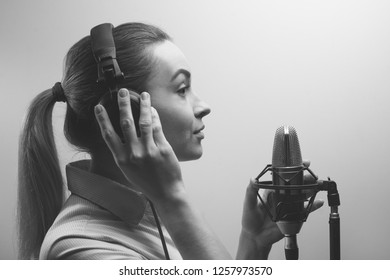 Young beautiful girl records vocals, radio, voiceover tv, reads poetry, blog, podcast in the studio on the studio microphone with headphones on a white background. Black and white photo