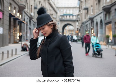 Young beautiful girl with red bag, wearing a black hat and leather coat, near the wall of the shopping center