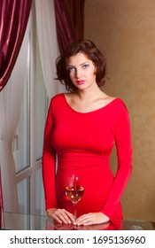 Young beautiful girl in a red dress with a glass of wine