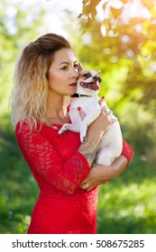 Young beautiful girl in red dress holding a dog Chihuahua summer on a warm Sunny day outdoors in the Park
