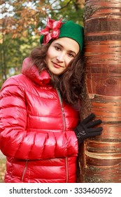 Young beautiful girl in a red jacket and a green beret in autumn park for a walk