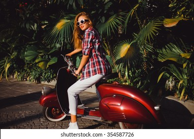 young beautiful girl in a red plaid shirt wearing sunglasses with red lipstick white jeans and sneakers posing on a red Vespa scooter near palm trees on the streets of Italy