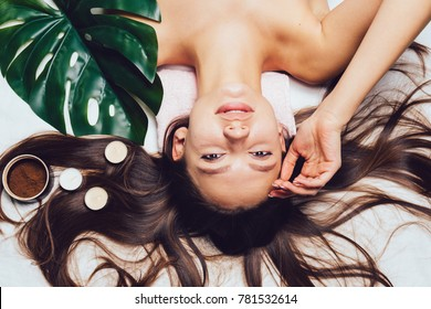 young beautiful girl relaxes, scented candles, coffee scrub, day spa