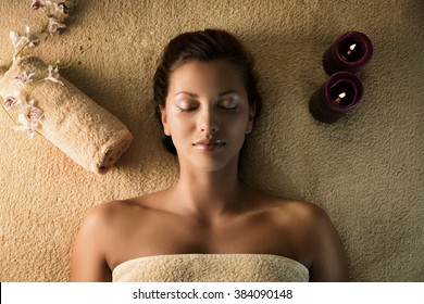 The young beautiful  girl relaxes in the spa. Nice setup of the candles and towels