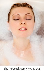 Young beautiful girl is relaxing in a bathtub with foam