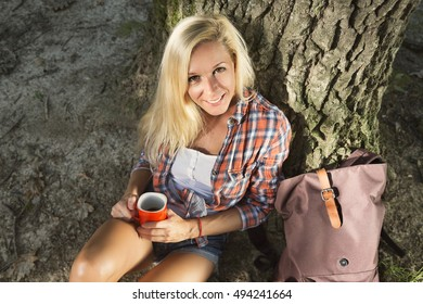 Young beautiful girl resting at the base of the tree