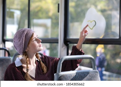 Young beautiful girl in retro style clothes draws a heart on a window in a moving tramway