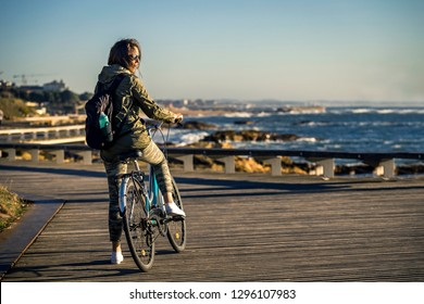 Young and beautiful girl is riding a bike by pier next to the Atlantic ocean during sunset time. Beautiful light. Smiley face. Porto, Portugal.