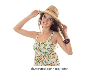 young beautiful girl in sarafan with floral pattern and straw hat looking and smiling on camera isolated on white background