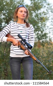 Young beautiful girl in a shooting glasses holding a sniper rifle