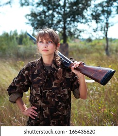 Young beautiful girl with a shotgun looks into the distance in an outdoor