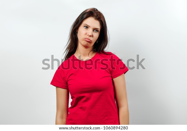Young, beautiful girl, shows an emotion of disappointment, sadness, apathy. Isolated on a light background. Different human emotions, feelings of facial expression, attitude, perception, body language